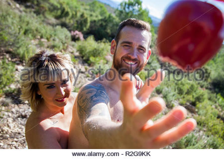 Young heterosexual couple poses naked in nature as Adam and Eve with the apple - Stock Image