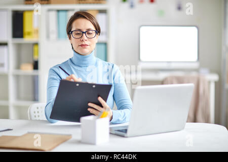 Young confident secretary or office manager sitting by desk and writing down business plan in front of laptop - Stock Image