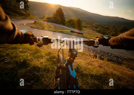 Cropped image of biker holding bicycle handle on field - Stock Image