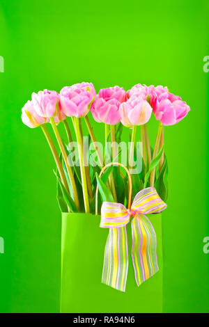 Flower bouquet of pink tulips in a vase with a multicolored bow tie on a bright green background, spring template for florists - Stock Image