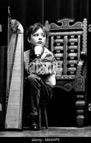Young girl in solo instrument harp waits to perform on stage at small eisteddfod in village hall at Y Groeslon Gwynedd - Stock Image
