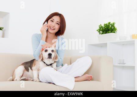 Young woman sitting with dog and on the phone, - Stock Image