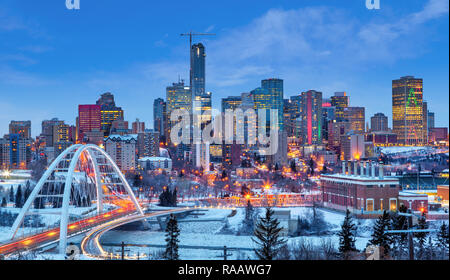 Edmonton downtown Winter skyline just after sunset at the blue hour showing Walterdale Bridge across the frozen, snow-covered Saskatchewan River and s - Stock Image