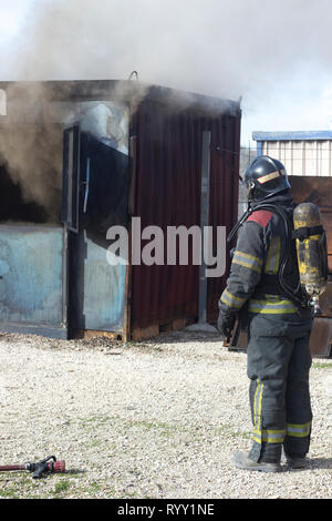 Firefighter putting out fire training station extinguisher backdraft emergency safety drill procedure. - Stock Image