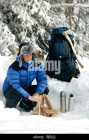 Woman making up a fire - Stock Image