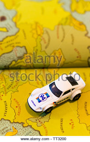 Mattel Hot Wheels white Nissan Fairlady car on a page with European map from a opened atlas book on circa June 2019 in Poznan, Poland. - Stock Image