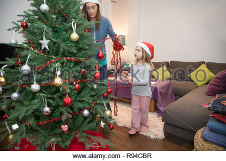 woman decorating a Christmas tree at home with four years blonde cute child with red Santa Claus hat - Stock Image