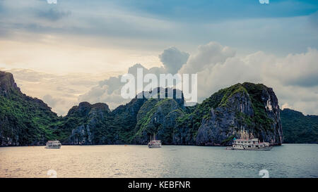 The storm clouds retreat over the limestone karsts just as the sun goes down in Halong Bay, Vietnam - Stock Image