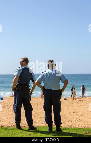Two New South Wales police officers watch a surf rescue recovery on Palm beach,Sydney,Australia - Stock Image