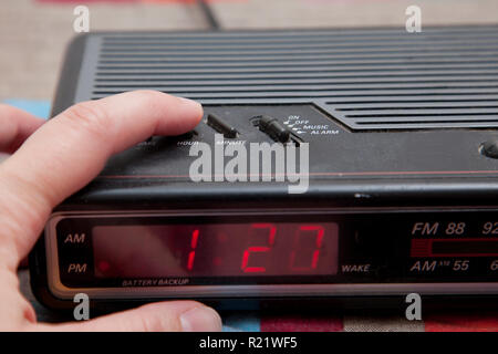 Finger changes an analog alarm clock shifting the hour back or forward - Stock Image