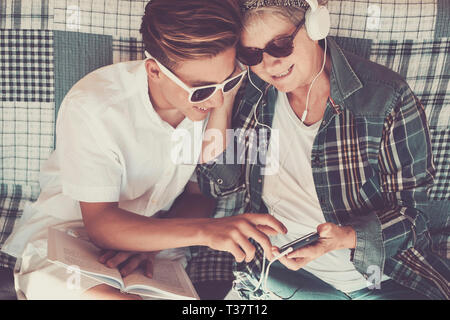couple young and old grandmother and teenager nephew family time together listen music with earphones and enjoy the day. Happy family and generations  - Stock Image