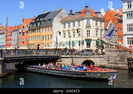 Tourists on canal tour boat passing under low bridge with colourful buildings in Nyhavn harbour, Copenhagen, Zealand, - Stock Image