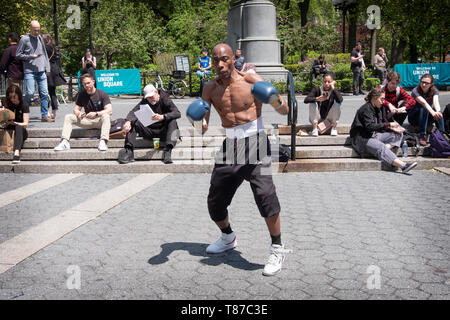 A very fit muscular 53 year old man shadow boxes and solicits donations for taking photos. In Union Square Park in Manhattan, New York City. - Stock Image