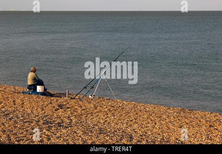 A lone fisherman,  on a shingle beach  near Sandown Castle, Deal, Kent - Stock Image