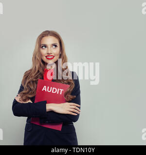 Happy business woman with audit report on gray background with copy space - Stock Image