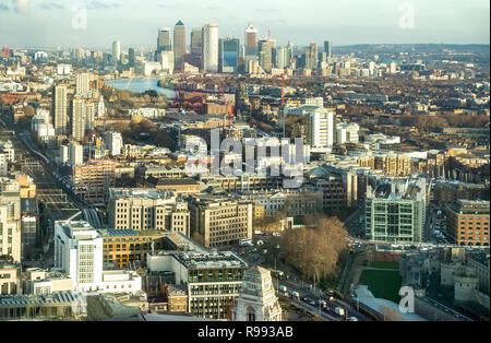 Elevated view over east London, St Katherine's Docks and Wapping towards they skyscrapers of Canary Wharf. The Tower of London is bottom right. - Stock Image