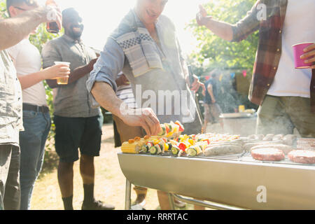 Male friends barbecuing in back yard - Stock Image