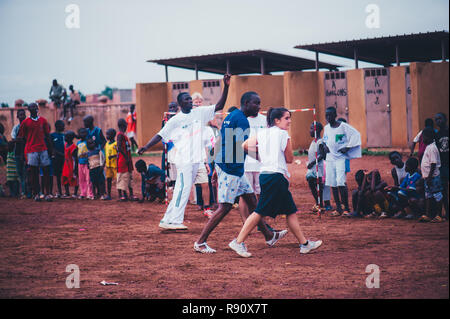 Mali, Africa - Black african children, boys and adults playing soccer with caucasian volunteers in a rubbish dump. Rural area near Bamako - Stock Image