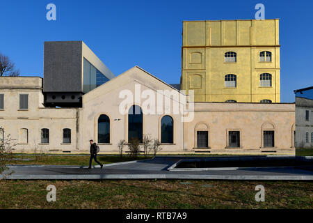 A person walking across Adriano Olivetti square, in the new Symbiosis district. In the background, the Fondazione Prada complex with the Haunted House - Stock Image