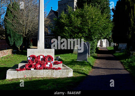 War memorial and poppies in the churchyard of St Peter's Church, Bishop's Waltham, Hampshire, England UK - Stock Image