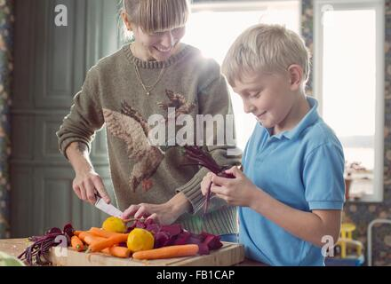 Mother and son preparing organic vegetables in kitchen - Stock Image