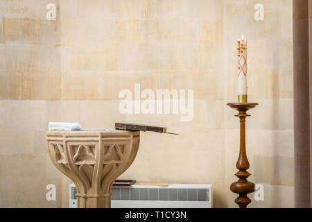 Opened baptismal font and a lit church candle ready for a Christening to take place inside Arundel Cathedral, West Sussex, England, UK - Stock Image