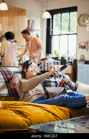 Smiling, affectionate couple watching TV and eating popcorn on living room sofa - Stock Image