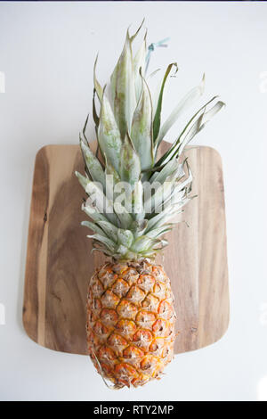 A pineapple in a flat lay layout on a wooden cutting board - Stock Image