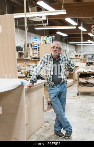 Portrait of a senior Caucasian carpenter in a large woodworking shoop. - Stock Image