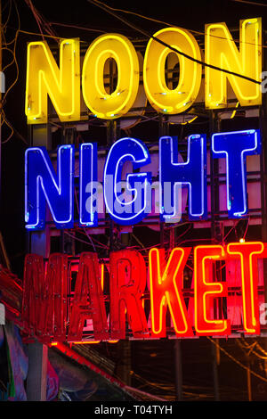 Bight colourful neon sign advertising a popular Noon Night Market in Siem Reap, Cambodia. - Stock Image
