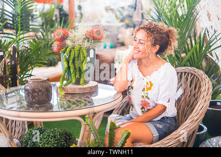 Young woman with blond curly hair sitting on a wicker chair with many plants admires the vegetation. Relaxation and leisure concept for people enjoyin - Stock Image
