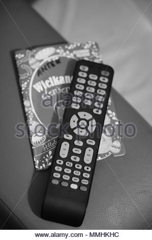 Television remote on a small book in soft focus and monochrome colors - Stock Image