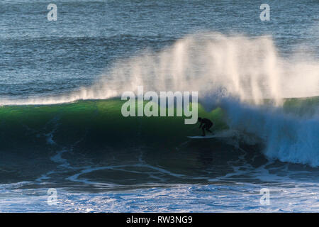 A surfer riding a big wave off the coast of Newquay Cornwall. - Stock Image