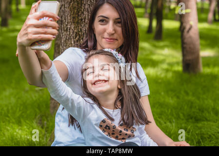 Young mom and little girl takes selfie together.Happy mother and daughter moments with love and natural emotion.Photo of young mother and her daughter - Stock Image