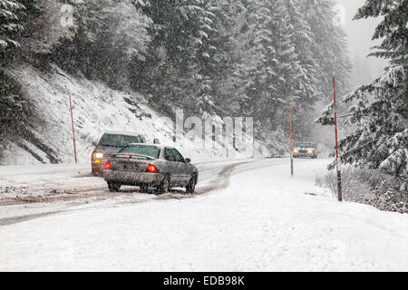 Cars stalled on road without snow chains blocks oncoming cars during snowstorm on the Tombstone Pass in Oregon Cascades. - Stock Image