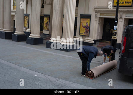 Carpet fitters carry off a rolled-up new carpet again after trimming it for the interior of the Lyceum Theatre on Wellington Street, on 5th March 2019, in London, England. - Stock Image