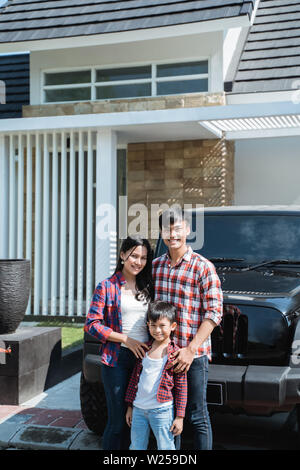 young asian family with kid in front of their house and car - Stock Image