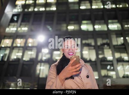 Smiling businesswoman using smart phone below urban highrise at night - Stock Image