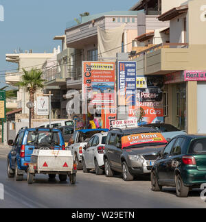 Chania, Crete, Greece. June2019. The busy seaside town with car rental office in the main street of Kalamaki a suburb of Chania, Crete. - Stock Image