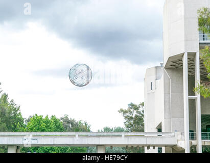 A floating sphere hangs over a walkway in front of the National Gallery of Australia.  A piece of public art called - Stock Image
