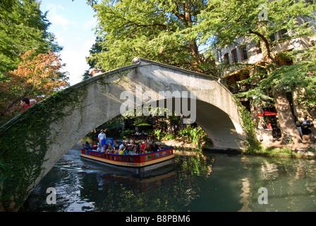 San Antonio River Walk riverwalk tour boat with tourists passes under arched bridge crossing the San Antonio River - Stock Image