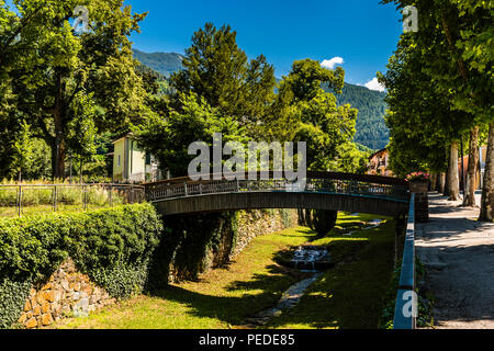 Summer river channel and bridge at Levico Terme, Trentino, Italy - Stock Image