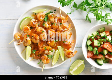 Grilled shrimp skewers with sauce and fresh vegetables. Prawns skewers and vegetables salad from sliced cucumber and tomatoes on white plate over wood - Stock Image
