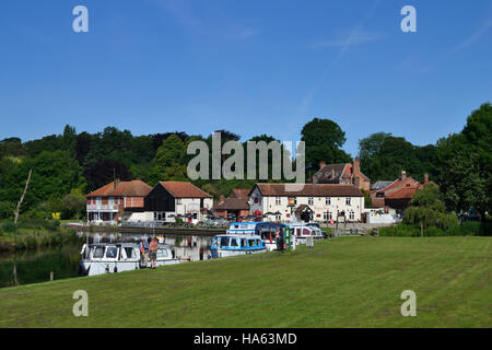 Boats moored at the staithe on the River Bure at Coltishall Common with the Rising Sun pub beyond on the Norfolk - Stock Image