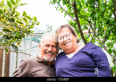 Portrait of cheerful happy senior aged couple smiling and having fun together in the garden looking at camera - retired lifestyle for nice caucasian p - Stock Image