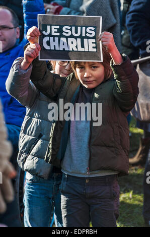 Geneva, Switzerland. 8th January 2015. Two children attend a vigil in Geneva's Place de Neuve, holding up a - Stock Image