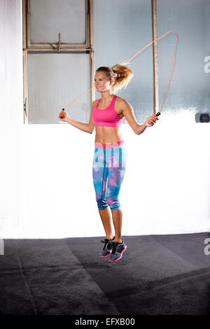 Young woman skipping in gym - Stock Image