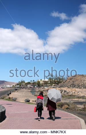 Two woman tourists walking along the sea front walkway at Playa Blanca, Lanzarote on a hot day. One is using an umbrella to protect her from the sun - Stock Image
