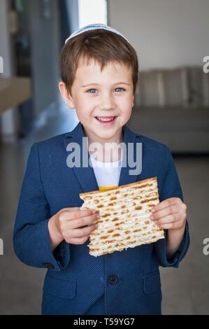 Vertical portrait of a cute Caucasian Jewish boy holding in his hands a piece of traditional Jewish matzo unleavened bread. Jewish Passover Pesach - Stock Image