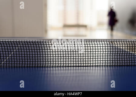 Black mesh tabletennis netting with a defocused background with a person walking away from the ping-pong table - Stock Image